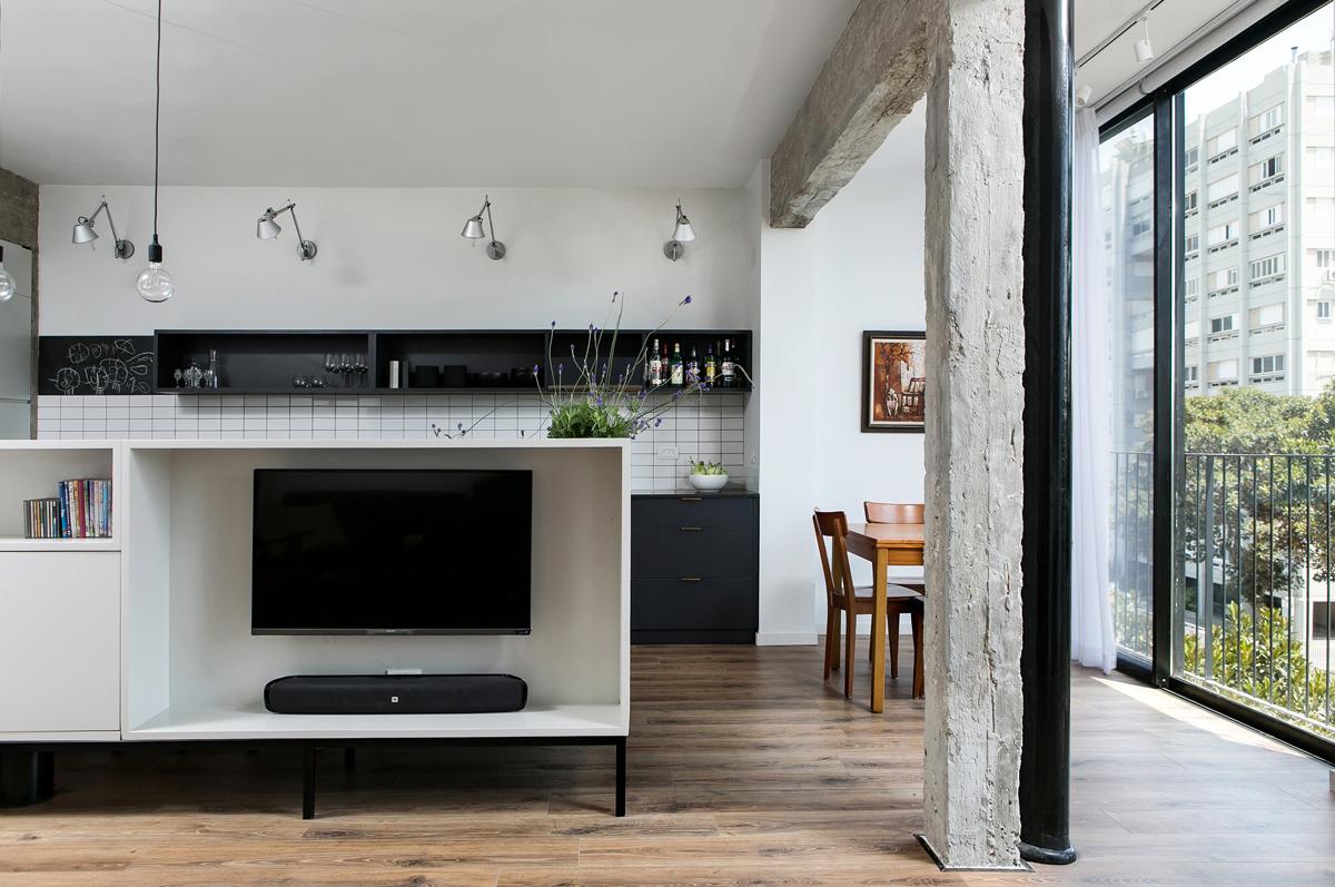 דירה לאב ובנו. רהיט מרכזי החוצה את החלל מאפשר הגדרת הסלון והמטבח כשני חללים נפרדים. צילום: שירן כרמל