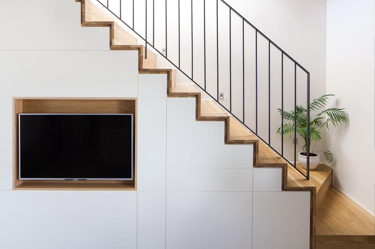 גרם מדרגות הולבש ונעטף ומתחתיו נוצר רהיט שמכיל טלויזיה, מקום אחסון וספרייה הפונה לצידו השני. צילום: טל ניסים